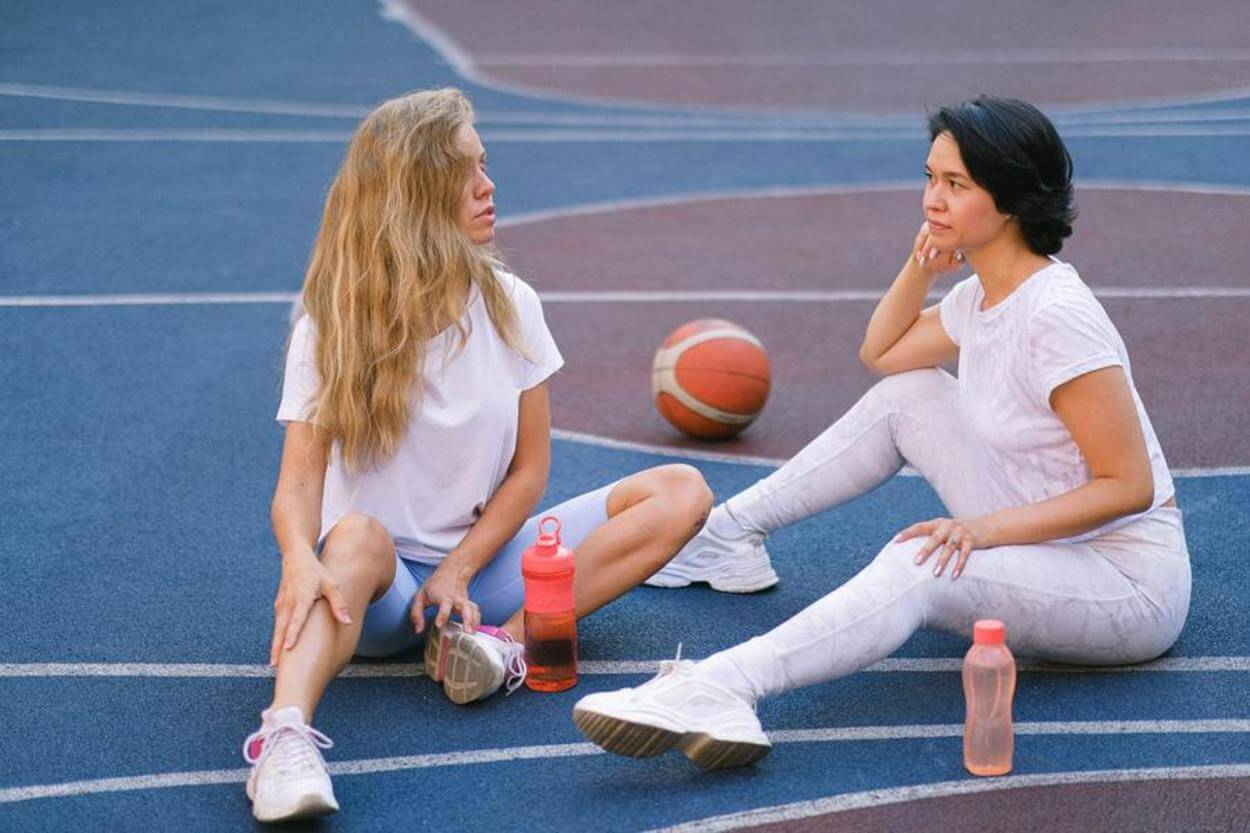 Two woman resting in the middle of a court, with their drinks.