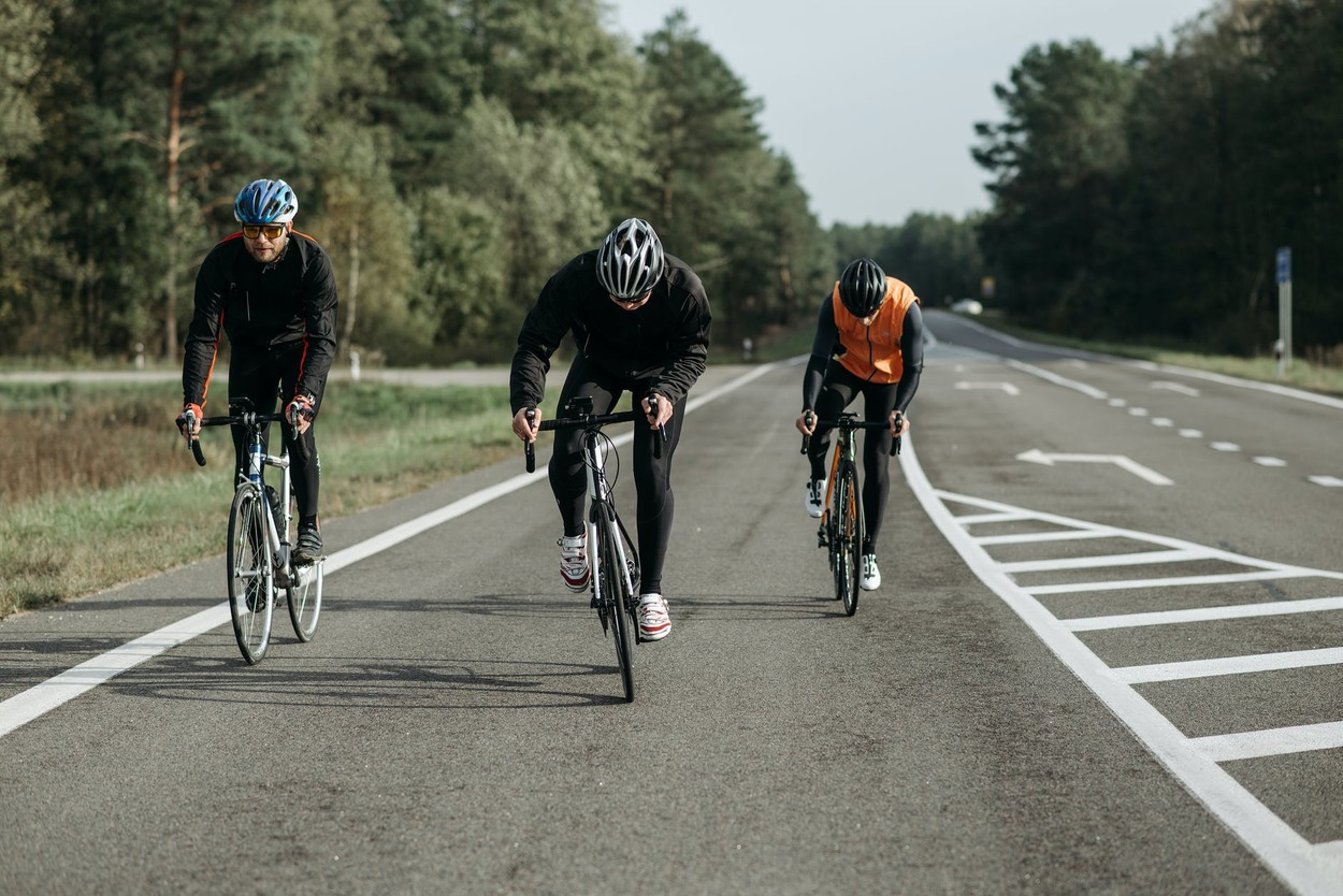 Three people biking on the road.