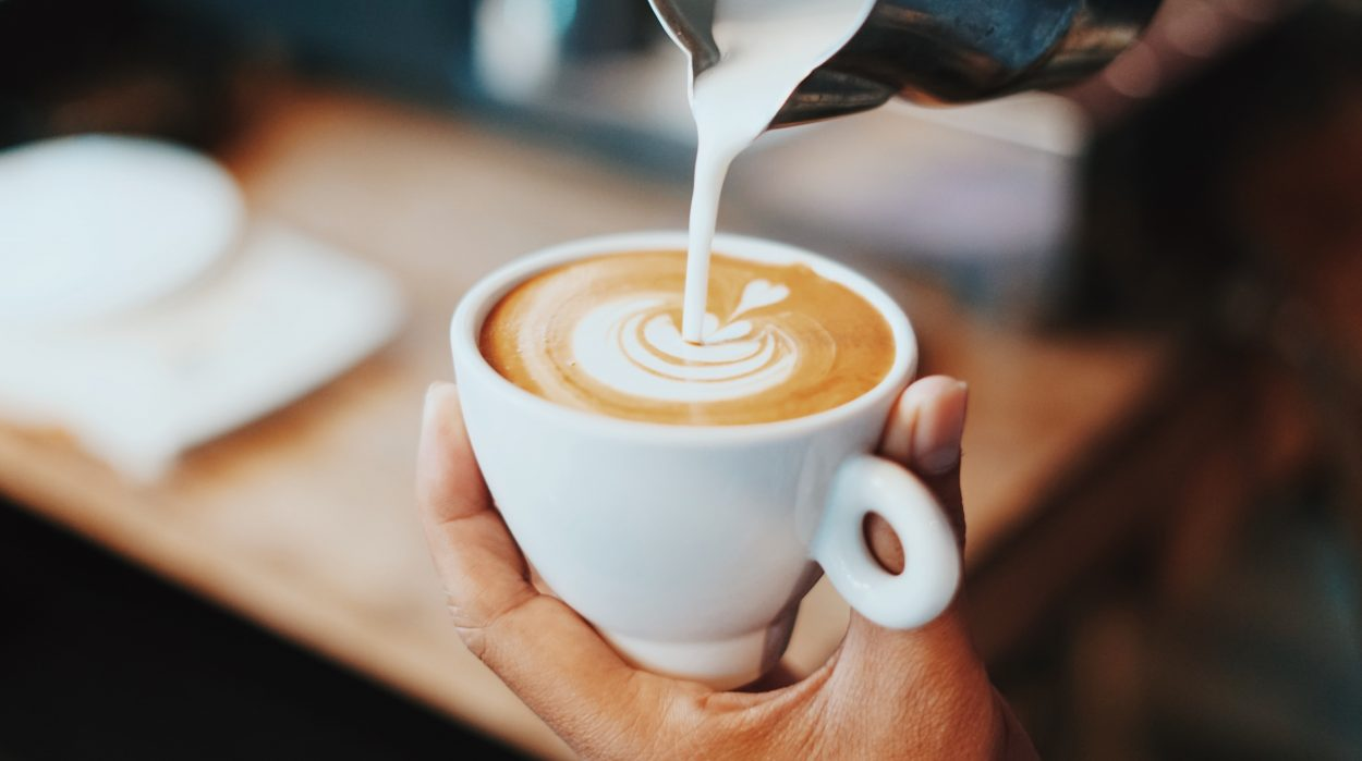 Milk being poured on coffee