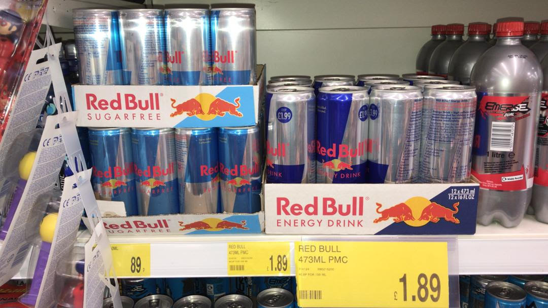 Packs of classic Red Bull energy drink and Red Bull Sugarfree displayed on a shelf